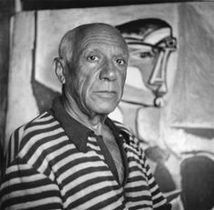 Spanish artist Pablo Picasso (1881 - 1973) in front of one of his paintings at home in Cannes in 1955.