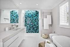 Blue fish scale tile feature wall in modern bathroom. Large heated towel rail, free standing bath and floating vanity.