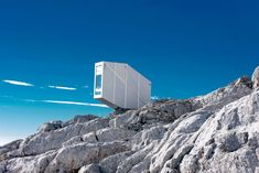 This tiny aluminium-clad cabin designed by Slovenian studio OFIS Arhitekti cantilevers over the edge of a mountain on the Slovenian-Italian border
