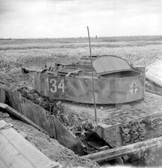 A knocked-out German PzKpfw IV Ausf H tank of 21st Panzer Division in a hull-down position, 13 July 1944