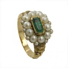 A Regency pearl and emerald cluster ring with ornate gold scrollwork shoulders, circa 1810