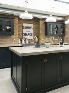 A perfect mixture of brick walls, 'Pantry Blue' cabinets and 'Bella Brass' handles