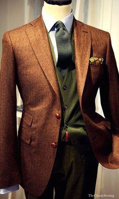 Abito formato da una giacca bordeaux ad un petto conrever a lancia, un gilet verde  militare e un paio di pantaloni classici scuri