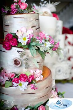 The look of birch tree bark accented with real flowers -- a beautiful rustic wedding cake.