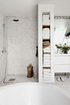 How to make the most of a small bathroom; I love the in wall storage for towels instead of a linen closet Maybe a bit too cold, but really like way to break up areas in bathroom with towel storage.