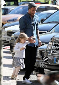 Stylish:Beckham looked typically stylish in a denim shirt and beanie hat as he guided the three-year-old towards their car during a brief outing in the north London suburb