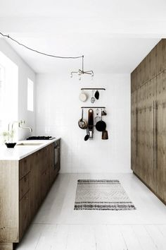 Wooden cabinets and white tiles in the kitchen of Danish carpenter and designer Kim Dolva of Københavns Møbelsnedkeri.