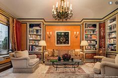 This lavish Fifth Avenue living room has patterned carpets, neutral furniture, built in shelving, heavy drapes, ornate moldings and colorful walls.
