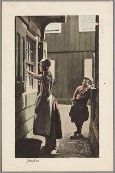 Jongen kijkt naar vrouw in dracht die ramen lapt in een steegje. 1910-1920 #NoordHolland #Marken