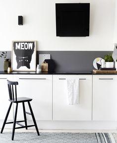 grijze strook als spatwand in combinatie met zwart werkoppervlak. Maakt de contrasten net iets minder hard