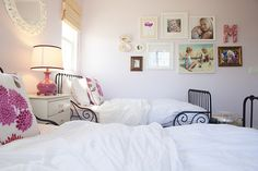 girls shared room w/ stand between and collage sister pics on wall