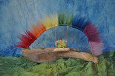 fairy swinging under rainbow