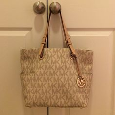 MK purse. MK purse. White and tan. One fray on the handle. A few interior make up stains but nothing anyone can see. I've kept this purse in very good condition for as long as I've had it. One of the side pockets has a whole sadly. Willing to trade, and take offers! Michael Kors Bags