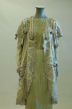 Description: A grey silk tapelace jacket, circa 1900, large gold and ivory woven label `Au Louvre' , the grey silk tape applied to an ivory filet mesh, the collar, hem and cuffs adorned with large crochet.