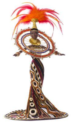 Fantasy Goddess of Africa <br /> Du designer américain Bob Mackie (Cher, CarolBurnett) <br /> Une tenue remplie de billes aux motifs tribaux africains et une riche coiffe de plumes. Certains costumes sont un hommage aux «petites mains» qui ont travaillé des heures sur ces vêtements miniatures.
