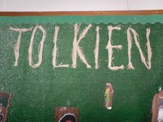 I tacked fake grass carpet to the bulletin board. I tied lengths of raffia grass with small pieces of raffia grass. I formed and stapled the letters as I went along, and I was pleased with the natural look of the letters.