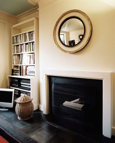 In the master bedroom, a convex mirror hangs above an unassuming fireplace.