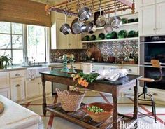 The French candlesticks and the 1940s French faience on the open shelves echo the green in the backsplash, made of 19th-century French concrete tiles purchased at Chateau Domingue, a store in Houston.