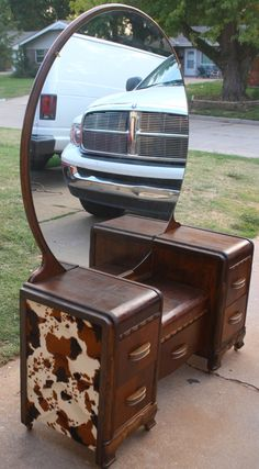 Vintage Antique Western Inspired Bedroom set. Art Deco Country style Water Fall Low Boy Vanity with round mirror. Matching Waterfall Wood Bed Frame. Beautifully stained with rustic Jaco Bean and lined with faux cow hide. The thick quality faux cow fabric gives these old solid wood vintage pieces a rustic Western Country look for anyone who loves country western theme for a guest room or bedroom
