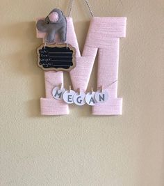 A 13.5 wooden letter wrapped twice in soft acrylic yarn with baby elephant embellishment. (Shown in picture is soft pink acrylic yarn with gray/pink baby elephant)Letter is perfect to hang on hospital door for baby birth announcement attached on letter is a small chalkboard with