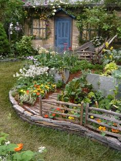 thoughtsforbees - stone house covered with greenery, chalky blue door, gorgeous raised garden with stone edging