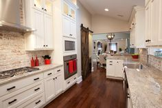 KITCHEN, AFTER: The kitchen has completely new cabinets with plenty of storage, high-end appliances, granite countertops, a barn door and new hardwood floors. The kitchen opens up to the dining room, making this galley kitchen feel more like an eat-in kitchen.