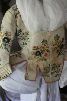 18th c French silk brocade caraco, lined with linen, edged with distinctive rose trimmed edge. This would have splayed out over a pannier widened skirt. The elbow length sleeves are trimmed with very rare original 18th c silk ribbon. Lined with linen. Pattern is expertly matched at front and back, green furry chenille is used to add dimension to the florals. Of course completely hand sewn and constructed.