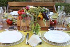 Para esta mesa, elegemos jogos americanos em palha amarela, sousplats transparentes, sobre os quais foram dispostos pratos em louça limoges branca. Descansos de talher em forma de legumes garimpados durante uma viagem à Paris e marcadores de lugar em forma de lousa da Antropologie.