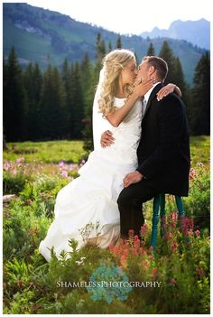 Beautiful wedding photo!! Love the mountainous background and wild flowers!!
