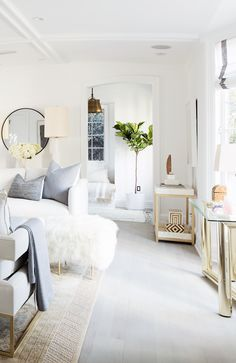 All-white living room with blonde wood and brass layered in.