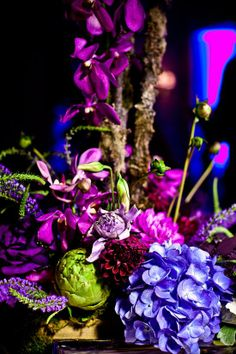 Arrangement with blue and purple flowers, plus artichokes for a pop of green!
