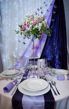 Esküvői asztal a lila különböző árnyalataiban. A hátfalat fényfüzérrel és pillangókkal díszítettük, a virágkompozíció pedig magas vázába került.