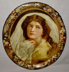 This is a large lithographed metal tray with the No. 12 at the bottom center. These trays were often used for advertising, although this one is plain. It shows a beautiful lady with a serene countenance. She is surrounded by a border of flowers and che...
