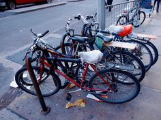 Streetworn, well-used bicycles with bag-covered seats chained to a bike rack near a busy street in N Bike Rack, Cycling, Busy Street, Bicycles, Fundraising, Police, Creativity, Friends, Bag