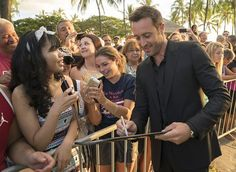 """Alex O'Loughlin who plays the part of  Steve McGarrett on """"Hawaii Five-0,"""" signs an autograph for a fan at Queen's Surf Beach in Waikiki Saturday, Sept. 12, 2014, in Honolulu. Thousands of Oahu residents and visitors gathered in Waikiki to watch the season five premiere of Hawaii Five-0 entitled A'ohe kahi e pe'e ai."""
