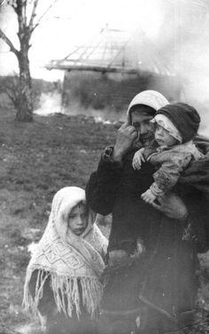 Женщина с детьми у сгоревшей хаты на Восточном фронте