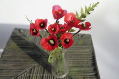 Stems of dollhouse scale corn poppies arranged in a miniature milk bottle made from recycled plastic