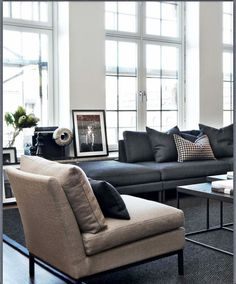 I love the sleek lines of this apartment which are accentuated by the modern furniture. I love the art actually propped against the wall as well as the gorgeous windows. Living Room Interior, Home Living Room, Apartment Living, Living Room Designs, Living Room Decor, Dream Apartment, Sofa Living, Masculine Living Rooms, Dark Sofa