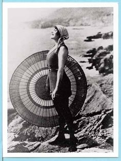 Annette Kellerman: Standing on a rock by the sea wearing a bathing suit and holding an open parasol (National Film and Sound Archive Australia | Title No. 558337-5)