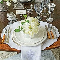 White Place Setting | A table set with scads of polished silver, crisp linens, fine china, and bamboo demonstrates the art of the mix, combining rustic and refined, old and new. | SouthernLiving.com