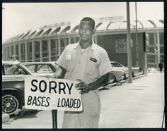 Parking attendant at the Seventh and Chestnut Streets lot standing beside a sign showing that parking for the St. Louis Cardinals game at Busch Stadium is full.  1966