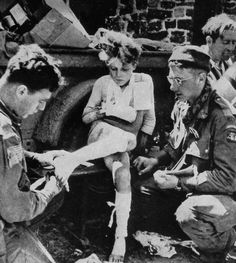 American medics treating a young girl, somewhere in Normandy, July 1944