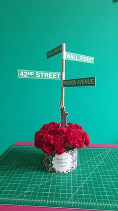 Centerpiece for a New York themed wedding. Mini flowers bouquet with NYC streets signs and Statue of Liberty