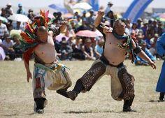 Dos luchadores bailan durante la Feria tradicional de Nadam en Xilin, en Mongolia.