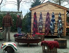 love the fire pit, large stumps & warm blankets. And the blanket hooks are genius! This is the coolest Christmas tree lot EVER! Great set up for cozy gatherings in your own backyard in fall/winter :)