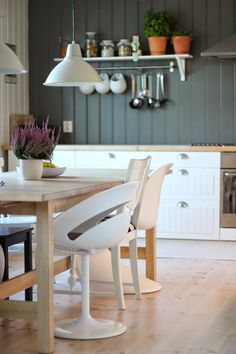 Kitchen, white cabinets, wooden countertop, wooden dining table with mixed chairs, white and gray planked walls, timber floor, modern farmhouse, scandinavian