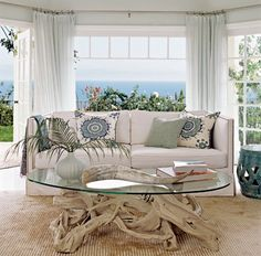 Light and breezy curtains, remarkable 'root' cocktail table, flooring the color of sand and beachy pillows.