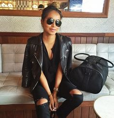 Sincerely Jules blogger wears ripped black jeans with a moto jacket, black top and oversized sunglasses.