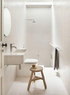 petite salle de bains blanche avec un miroir rond, un carrelage mural et de sol blanc et une douche italienne moderne