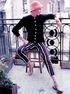 Model in striped pants and top sitting on balcony in Paris, photo by Genevieve Naylor, 1958